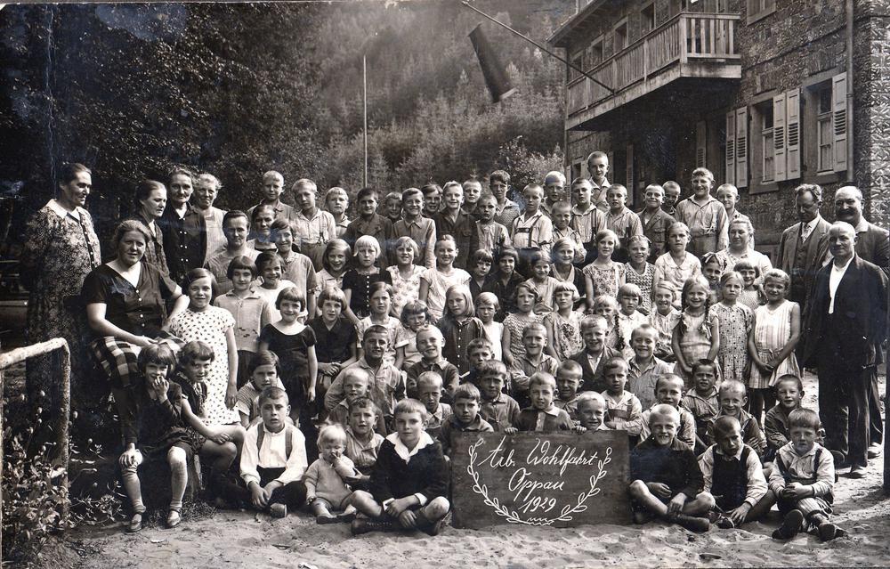 Schwarzweißbild einer großen Kindergruppe aus dem Jahr 1929, rechts und links umrahmt von Betreuern und Betreuerinnen.