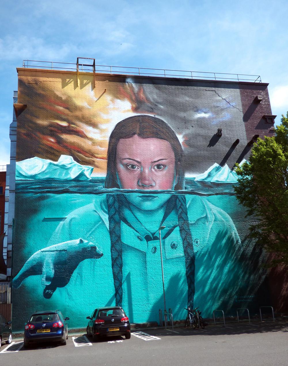 Gemälde mit einer Darstellung Greta Thunbergs auf einer Häuserwand über vier Stockwerke. Wie die Eisberge im Hintergrund ragt sie aus dem Wasser.