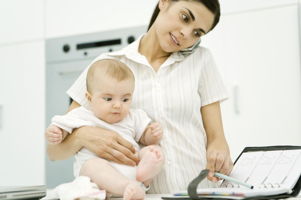 Frau mit Baby auf dem Arm, die in ihrem Kalender einen Termin notiert.