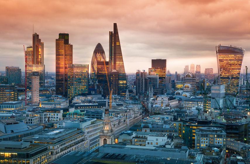 Das Bankenviertel von London mit vielen modernen Hochhäusern, deren obere Hälfte noch von der Sonne bestrahlt wird, währen der untere Teil im Schatten liegt.
