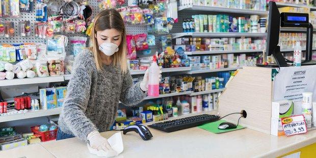 Eine Verkäuferin desinfiziert die Ladentheke in einem kleinen Geschäft. Sie trägt Gesichtsmaske und Handschuhe.