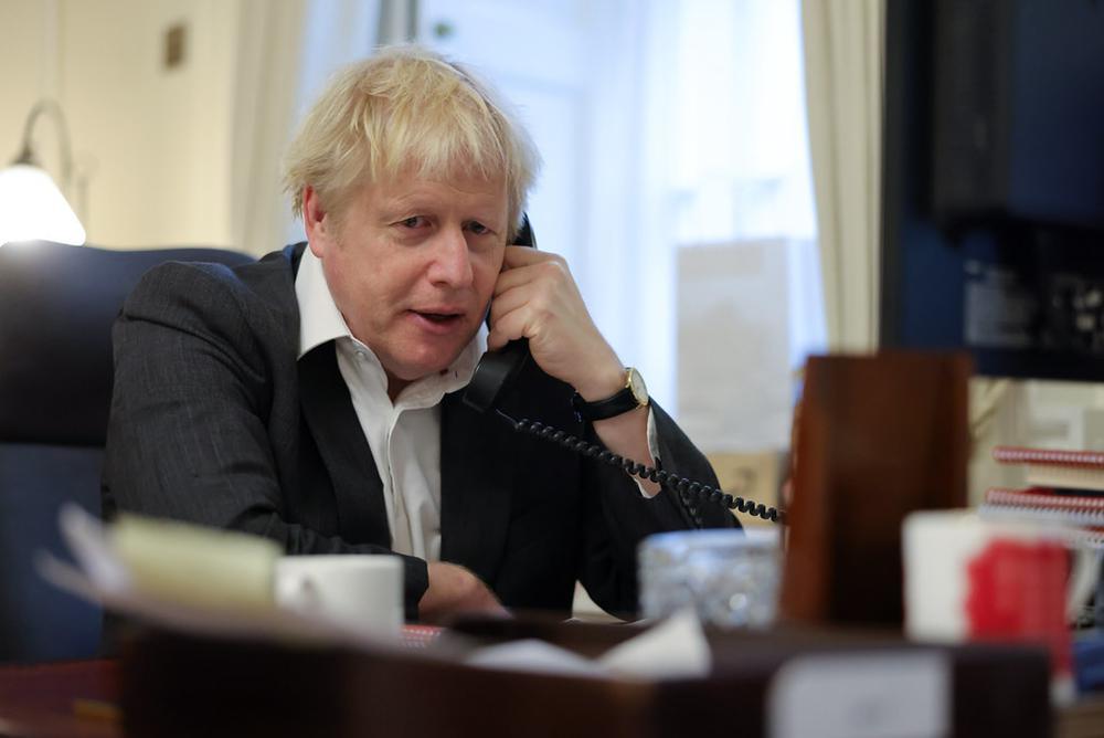 Boris Johnson sitzt an seinem Schreibtisch, in weißem Hemd, ohne Schlips, und spricht am Telefon.