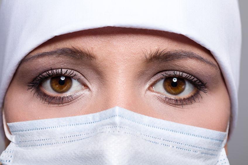 Gesicht einer Frau mit Maske, bei dem nur die Augen zu sehen sind.