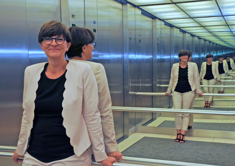 Saskia Esken steht in einem Fahrstuhl mit verspiegelten Wänden, so dass ihr Bild nach hinten hin mehrfach gespiegelt zu sehen ist.