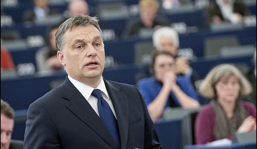 Victor Orban steht mit einem blauen Anzug und passendem Schlips in EU-Parlament, im Hintergund sind unscharf Abgeordnete zu erkennen.