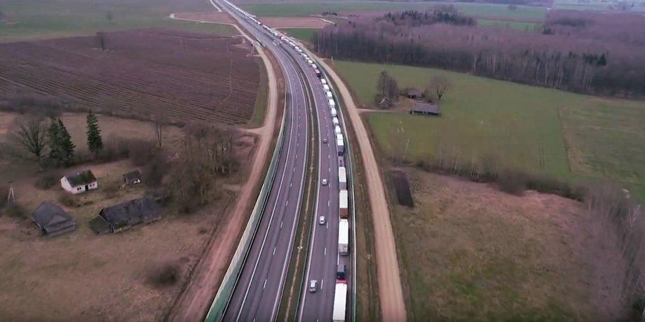 Luftaufnahme von einem Lkw-Stau auf einer Autobahn, der sich bis zum Horizont hinzieht.