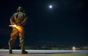 Ein Soldat in Tarnuniform steht als Bodenlotse auf einem Flugfeld in der Nacht, im Hintergrund ist ein Flugzeug zu erkennen.