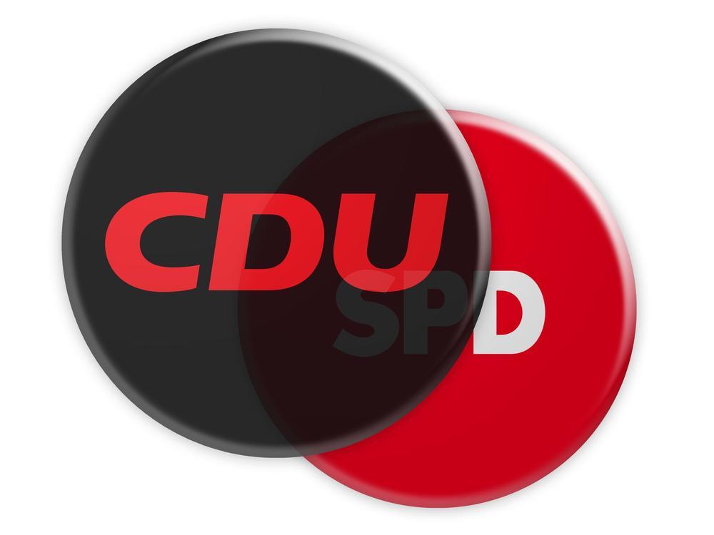 Eine schwarze Plakette mit der Aufschrift CDU verdeckt weitgehend eine rote mit SPD.