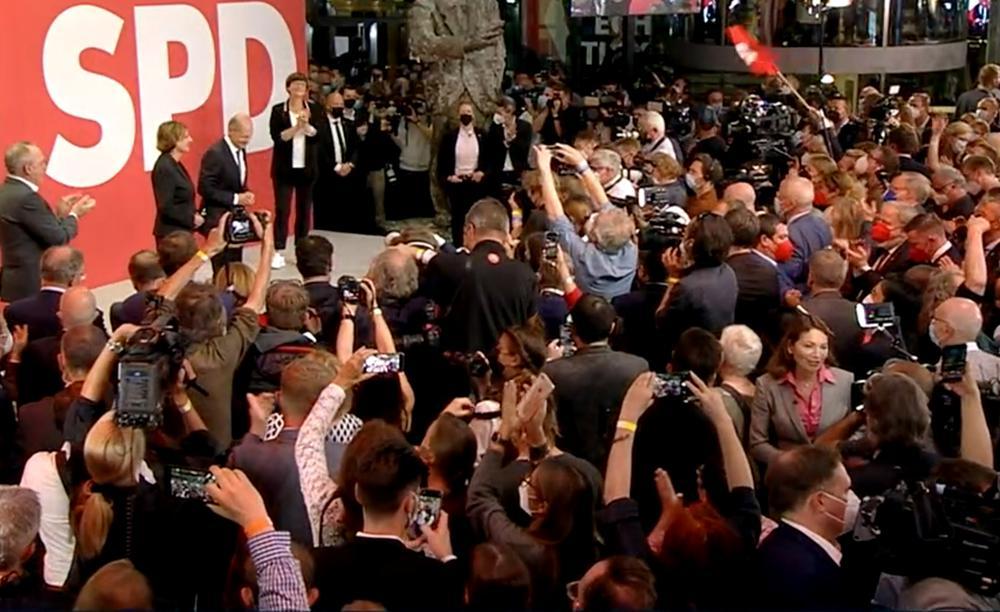 Blick von oben auf einen jubelnde Menge. Im Hintergund prangen groß auf rotem Grund die Buchstaben SPD.