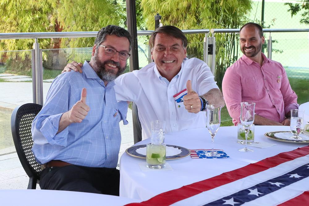 Jair Bolsonaro legt den Arm um die Schulter eines Mannes, der neben ihm sitzt. Der Tisch ist mit der amerikanischen Flagge in Rüschenform geschmückt.