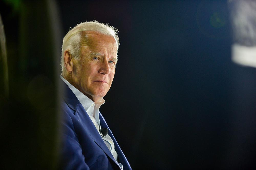 Joe Biden sitzt in einem blauen Anzug auf einer Bühne. Er ist von der Seite aufgenommen und blickt Richtung Kamera