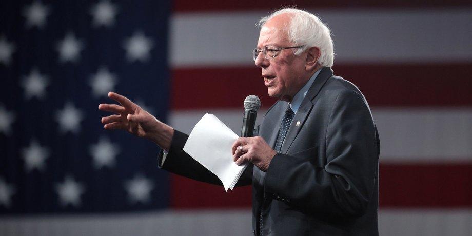 Bernie Sanders hält eine Rede vor einer USA-Flagge, den rechten Arm hat er Richtung Publikum ausgestreckt, in der linken Hand hält er ein Manuskript.