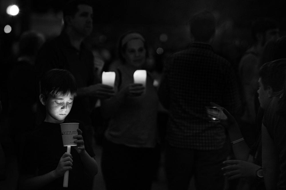 Auf einem düsteren Schwarzweiß-Bild sind Menschen unscharf zu sehen, ein Junge im Vordergrund links hält eine Kerze in einem Pappbecher.
