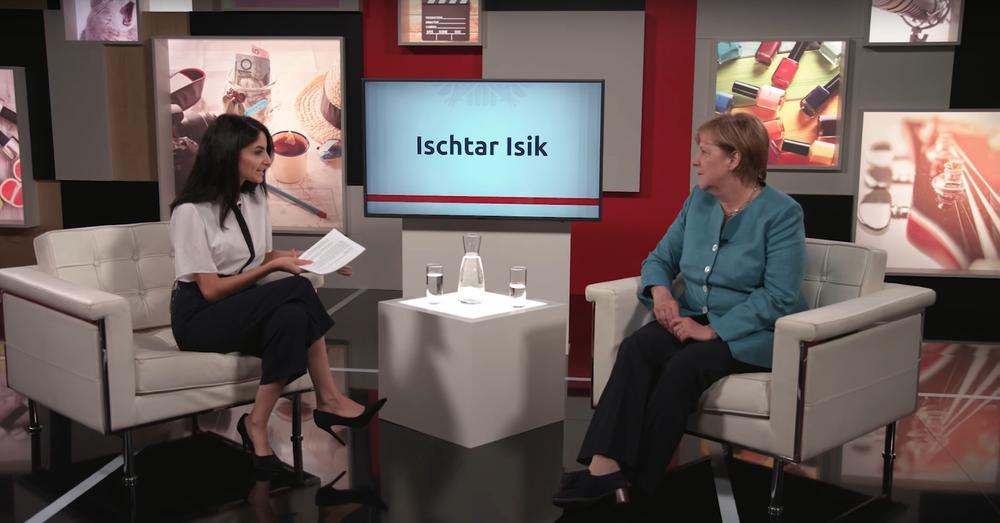 Ischtar Isik interviewt Angela Merkel. Beide sitzen sich in weißen Sesseln gegenüber vor einer Wand, auf der Fotos mit Nagellack, Gitarre oder Teetasse zu sehen sind.