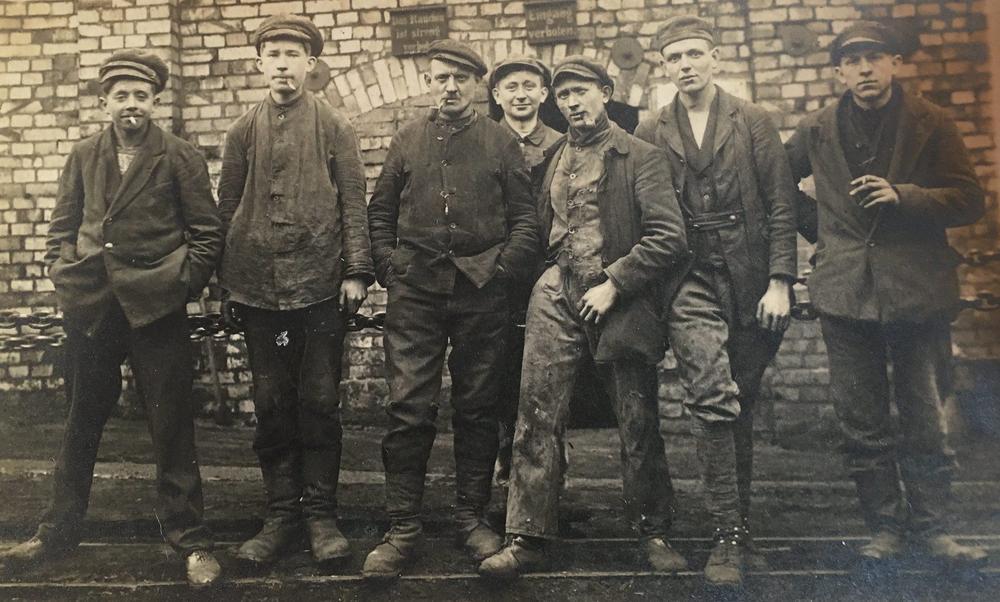 Arbeiter posieren in schmutzigen Arbeitsklamotten und rauchend für einen Fotografen; Bild in Schwarzweiß.