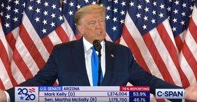 Donald Trump steht mit ausgebreiteten Armen hinter einem Rednerpult, im Hintergrund US-Flaggen