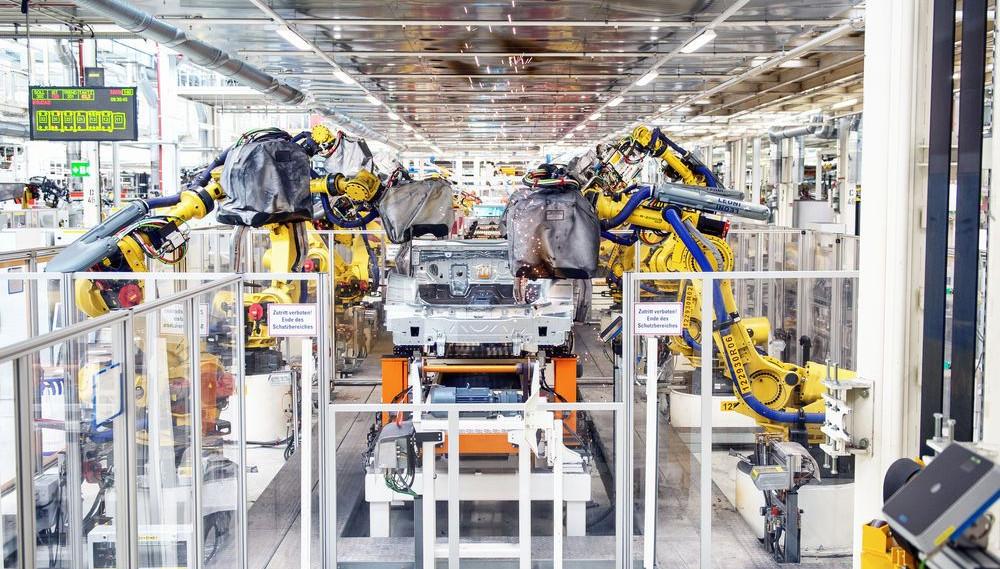 Blick in eine Autofabrik, in der Roboter rechts und links eines Fließbandes Karosserien zusammensetzen.
