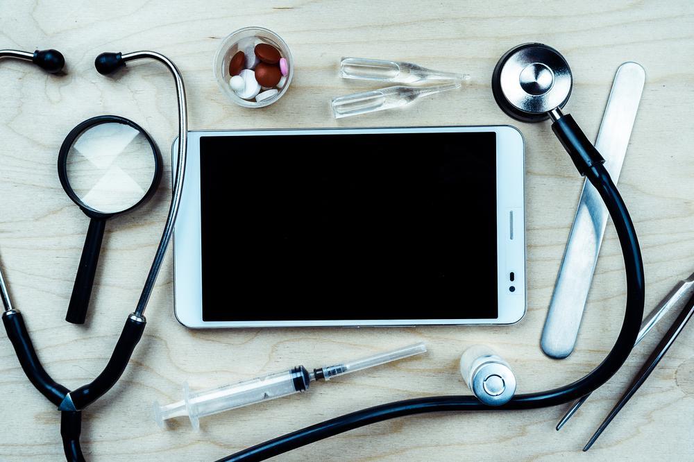 Stetoskop, Spritze, Pinzette, Tabletten, kleine Ampullen und ein iPad liegen auf einem Tisch