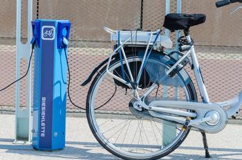 Ein Elektro-Fahrrad steht an einer Stromsäule und wird aufgeladen.