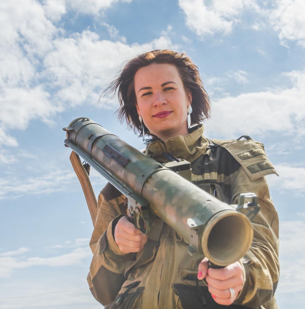 Frau in Uniform mit einer Bazooka, die freundlich in die Kamera blickt.