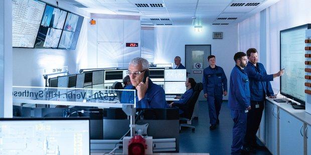 Kontrollraum mit vielen Bildschirmen auf Schreibtischen und an der Wand, Männer in blauen Overall überwachen das Geschehen, teils sitzend, teils stehend.
