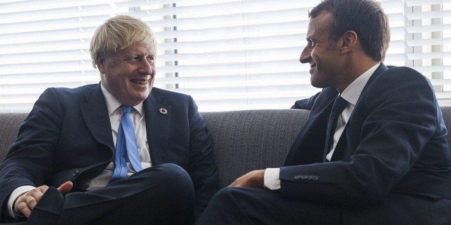 Boris Johnson sitzt neben Emmanuel Macron auf einem graublauben Sofa, beide tragen blaue Anzüge, weiße Hemden und blaue Krawatten.