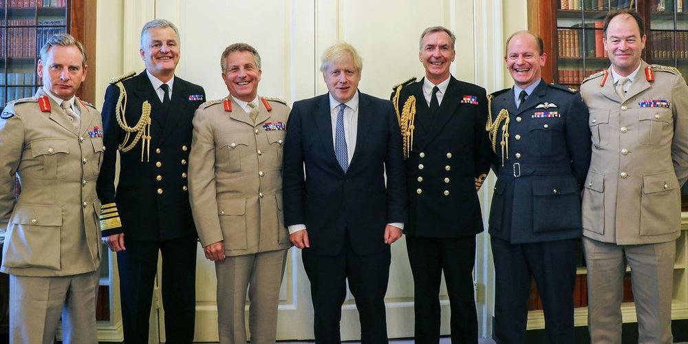 Boris Johnson steht mit den führenden Militärs des Landes in einer Reihe nebeneinander.