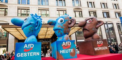 Karnevalsumzug mit Motivwagen zur AfD, auf dem drei Köpfe zu sehen sind. Der erste ist noch blau, der zweite blau-braun, der dritte ganz braun.