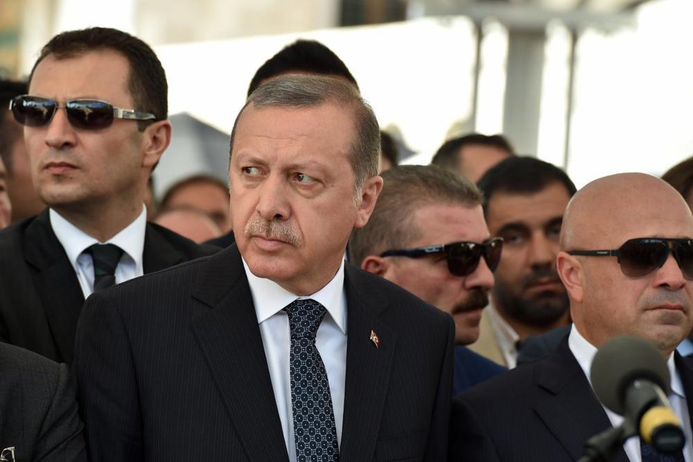 Der türkische Präsident Erdogan umgeben von grimmig blickenden Männern mit Sonnenbrillen.