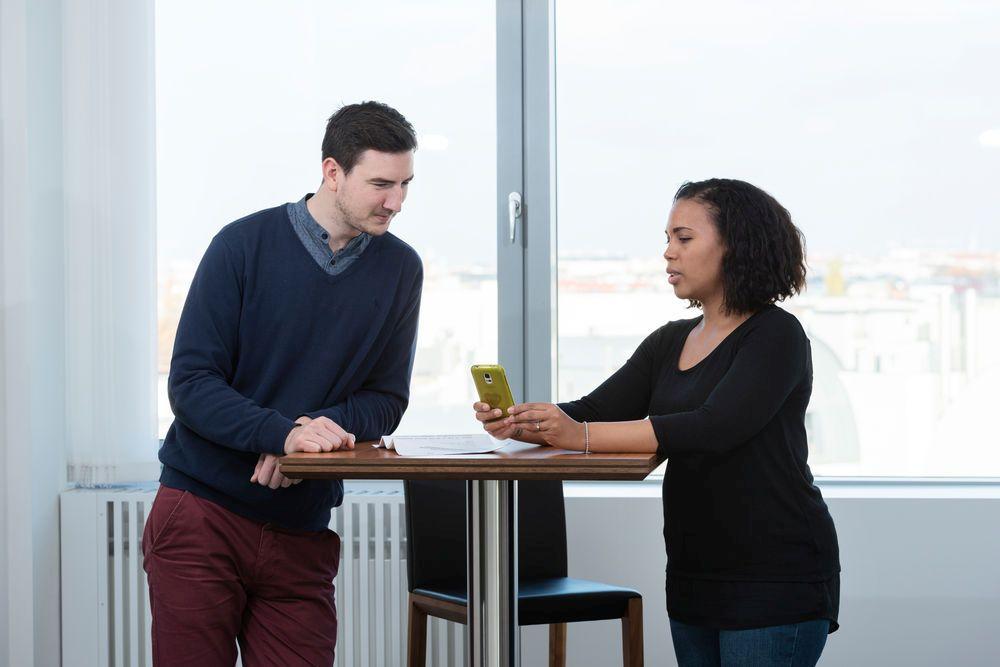Ein Mann und eine Frau stehen an einem Stehtisch und blicken auf ein Handy.