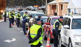 Polizisten kontrollieren Autos, die sich bis weit in den Bildhintergrund stauen.