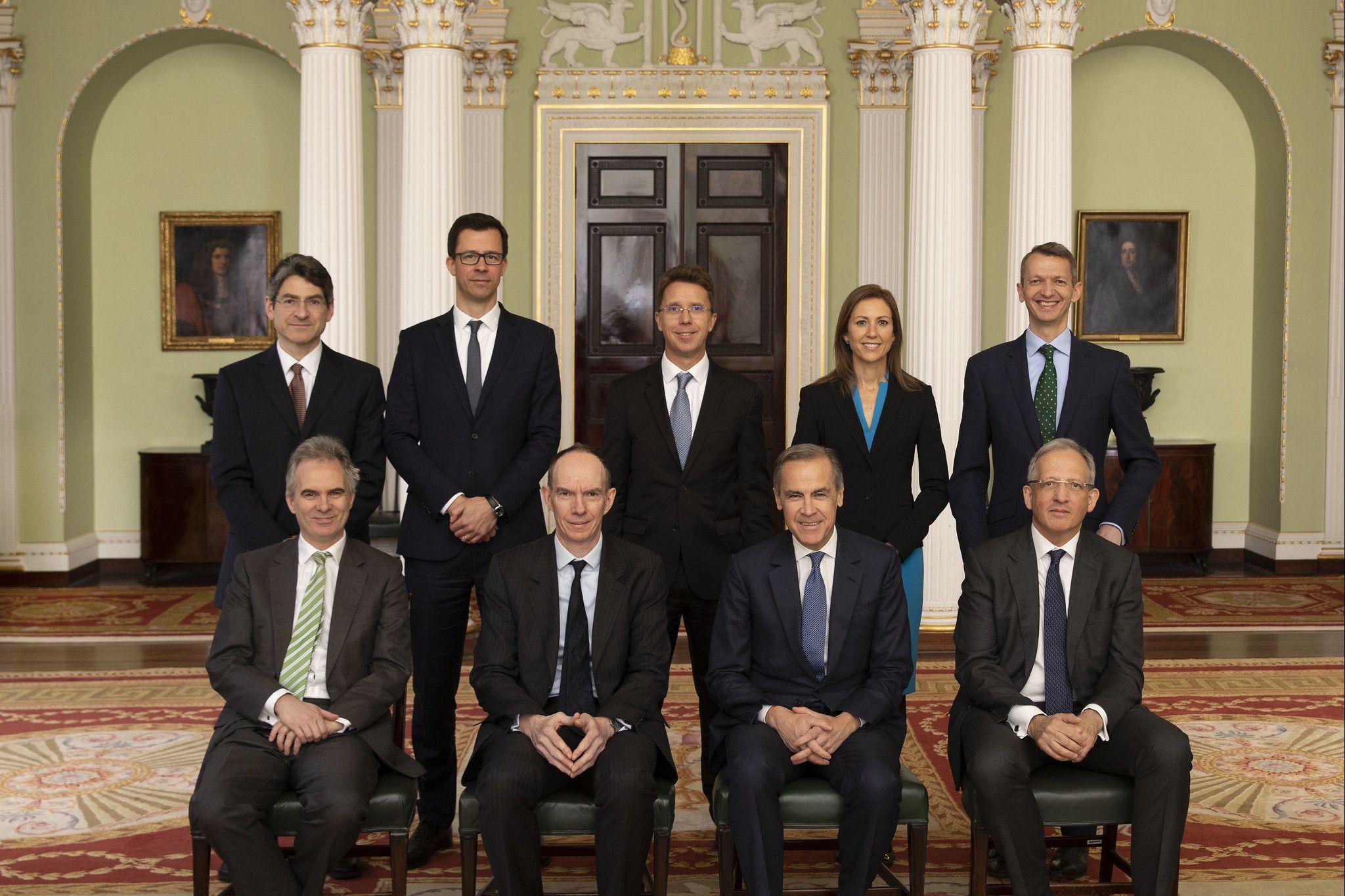 Bild einer Gruppe von neun Personen. In der vorderen Reihe sitzen vier Männer, dahinter stehten vier Männer und eine Frau. Alle tragen dunkle Anzüge bzw. die Frau einen dunklen Blazer