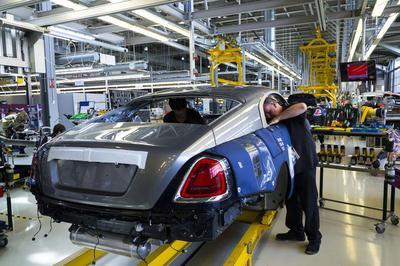 Autofabrik in England, in der Arbeiter sich in ein Auto auf dem Fließband beugt.