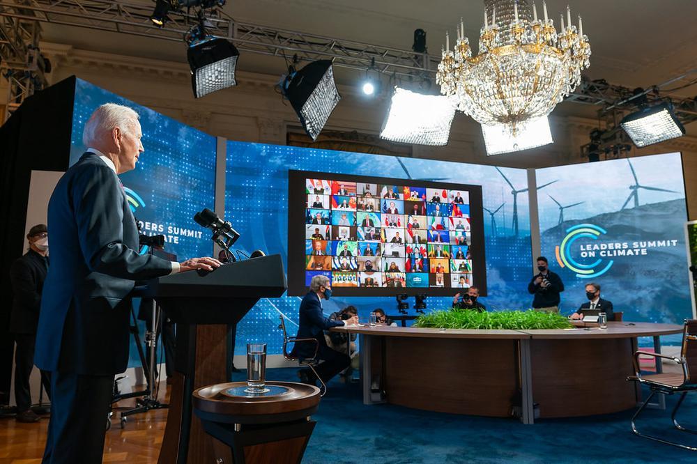 Joe Biden steht links auf einer Bühne und spricht. Rechts ist eine große Videowand, auf der viele Gesrpächspartner in kleinen Rahmen zu sehen sind, die hier zugeschaltet sind.