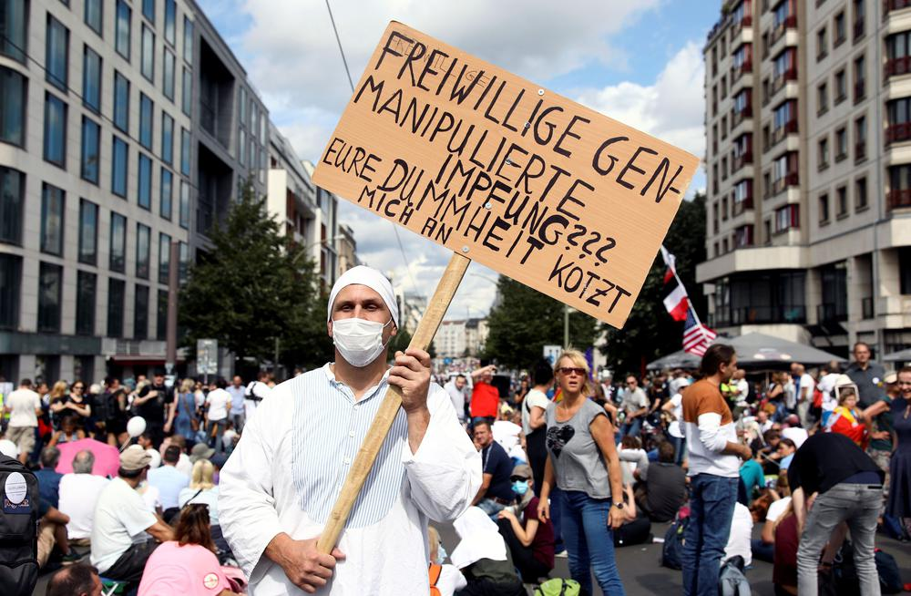 Straßenprotest, in der Mitte ein Mann mit einem selbstgemalten Pappschild, auf dem steht: Freiwillige genmanipulierte Impfung??? Eure Dummheit kotzt mich an.