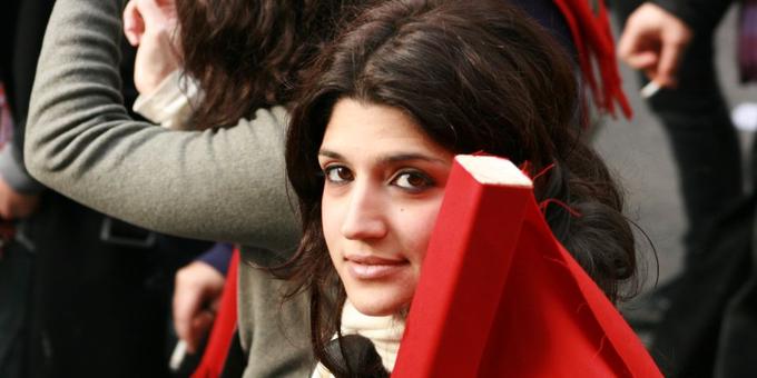 Griechische Demonstrantin mit roter Fahne im Arm.