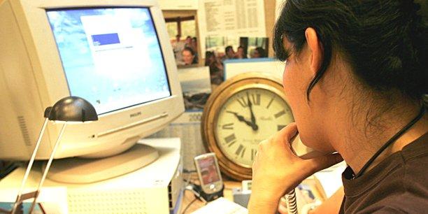 Frau an Schreibtisch mit Computer und Uhr